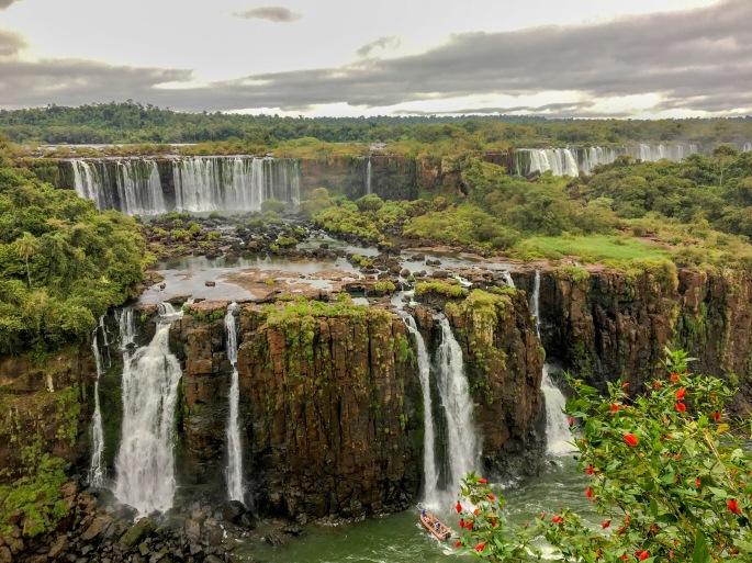 Quedas d'água nas Cataratas do Iguaçu. Um bote se aproxima de uma queda d'água, ficando embaixo dela.